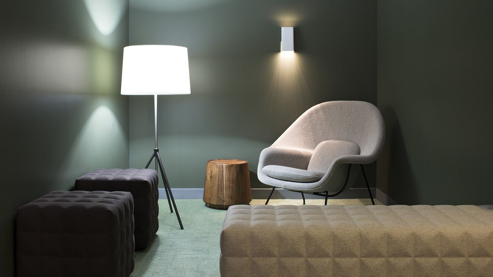 A dark green small room with a Knoll Womb chair, lamp, and cube shaped lounge furniture