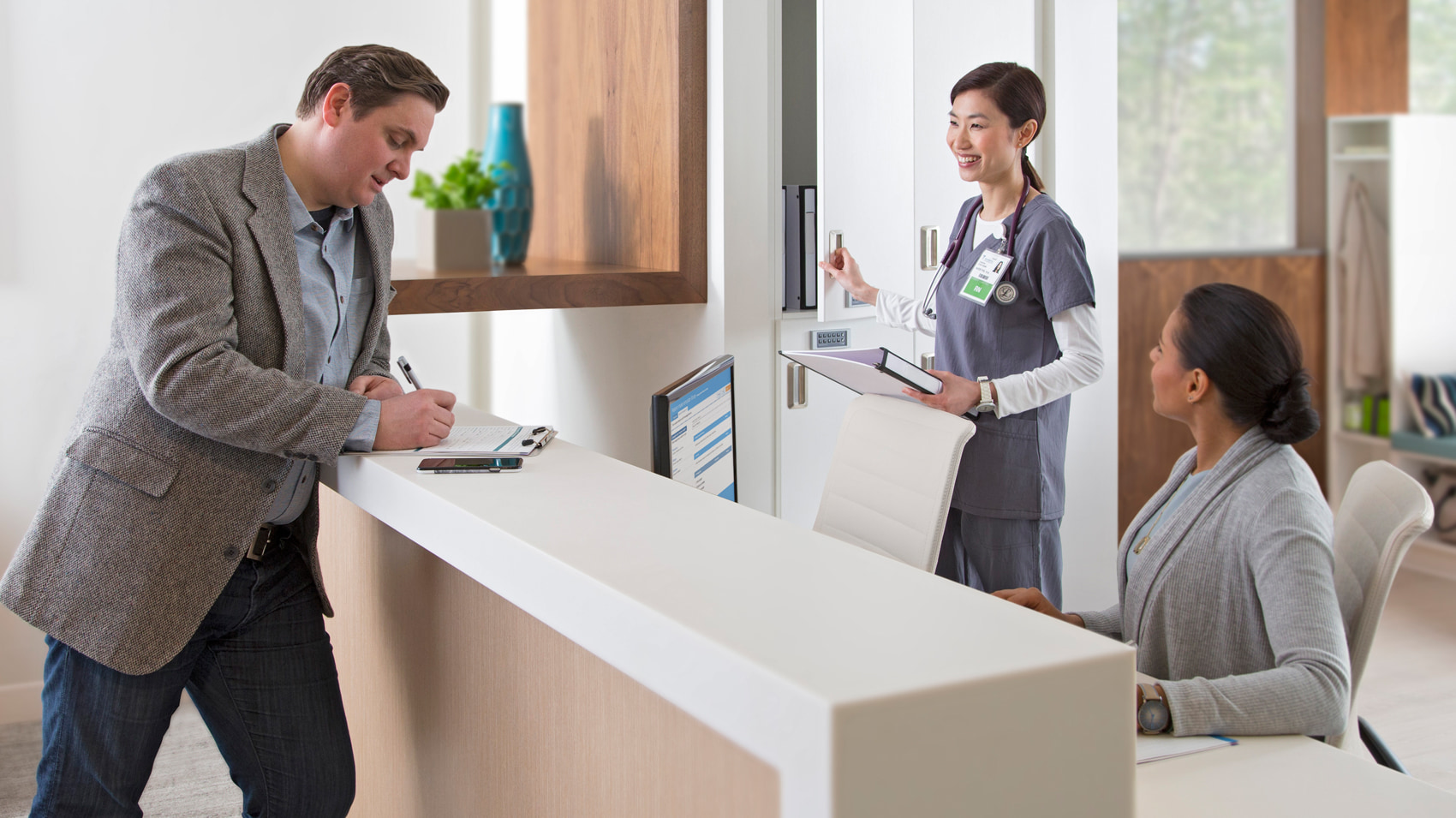 A man checking in at a clinic with a receptionist and medical personnel
