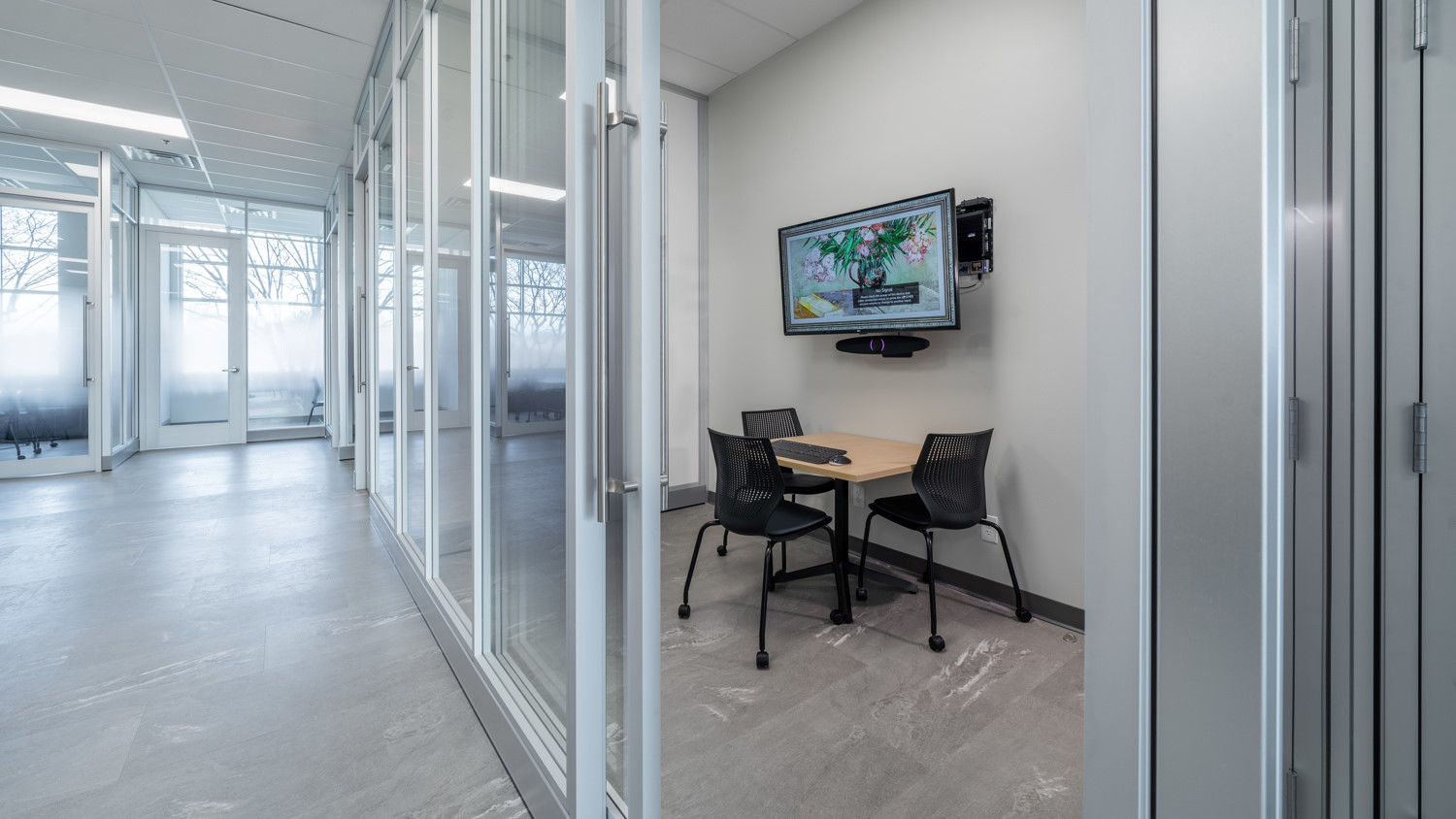 A office huddle space with demountable walls, table, chairs, and technology