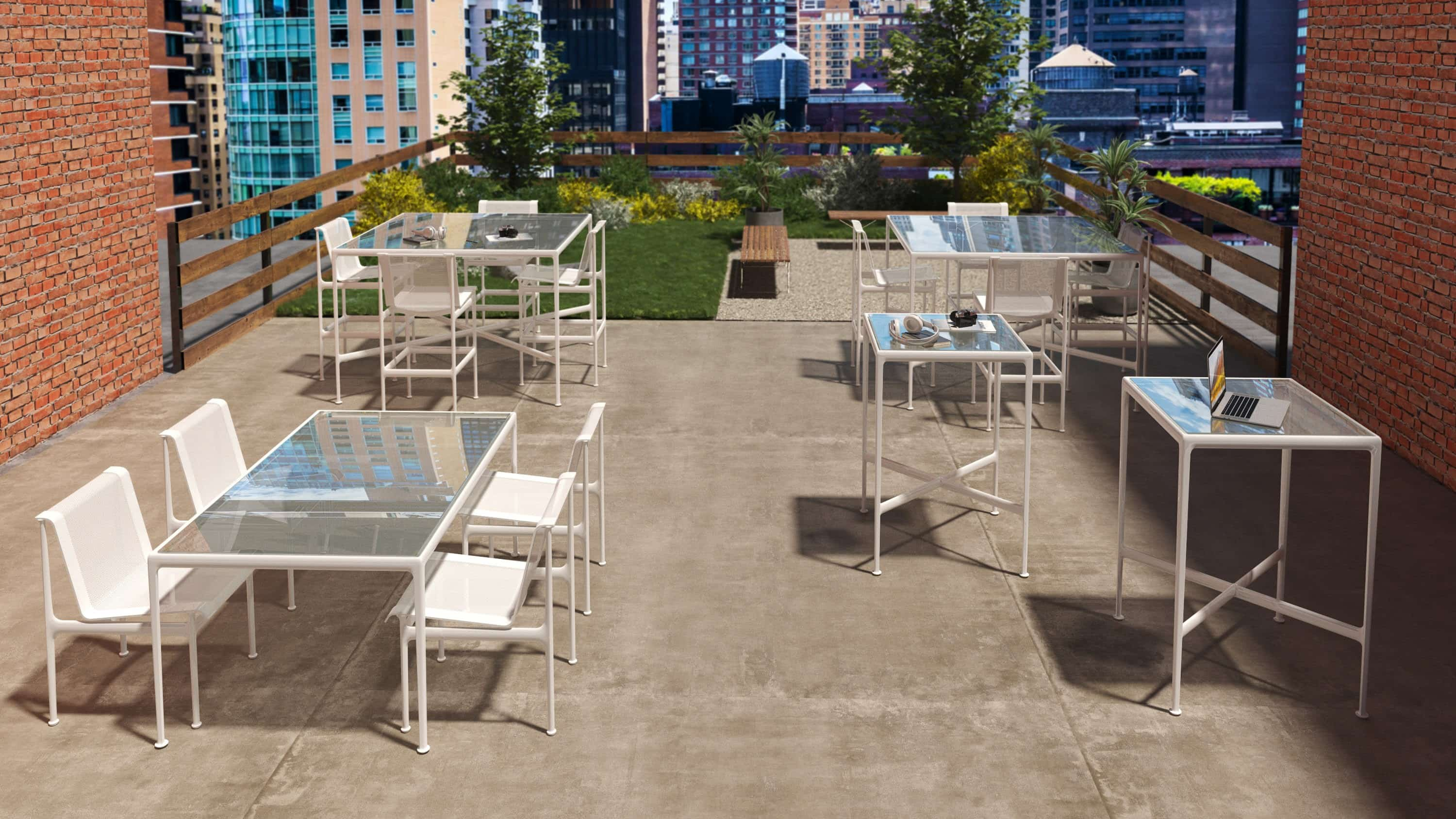 Outdoor patio with greenery, tables, and white chairs on a rooftop