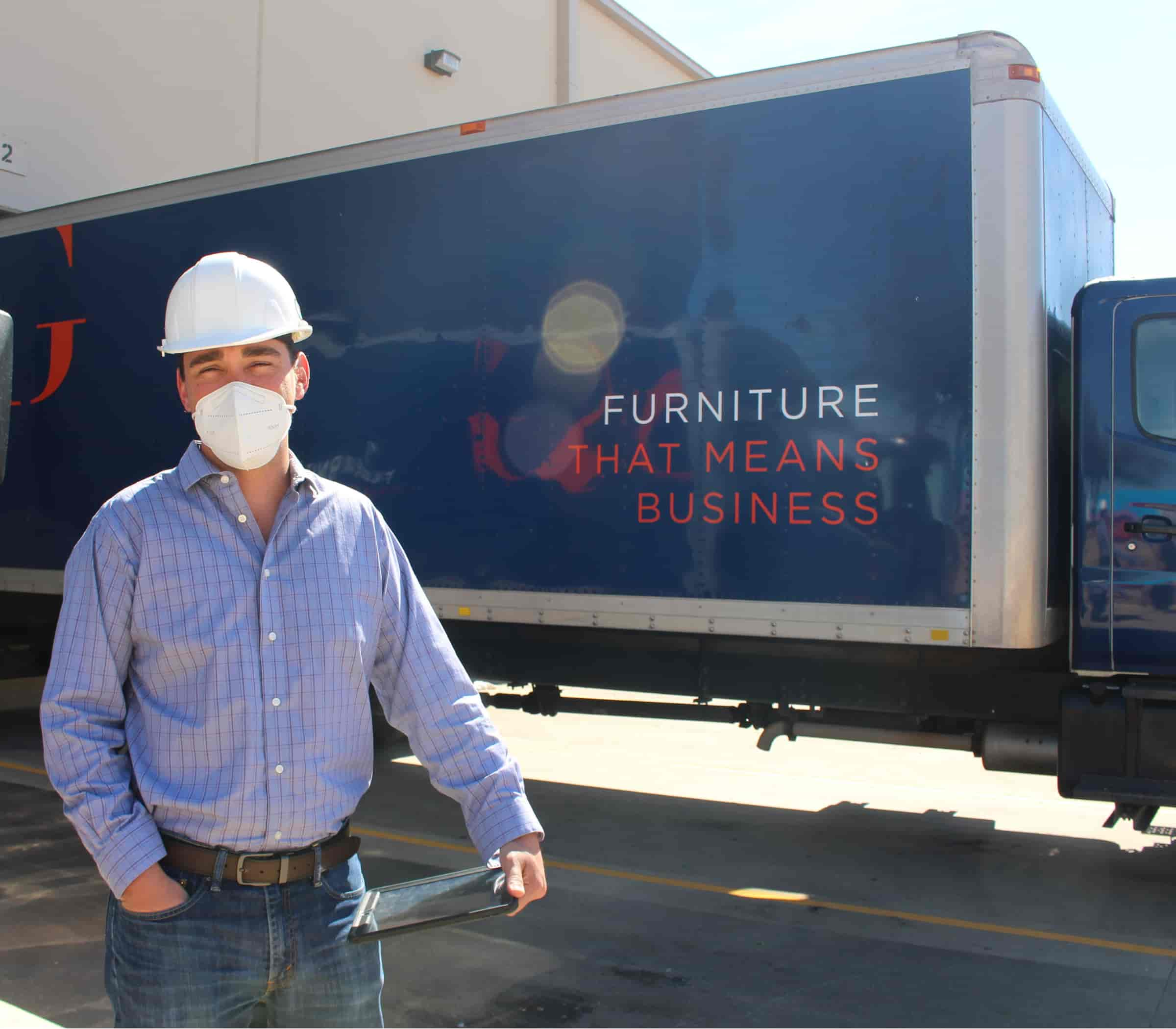 Project manager standing in front of a furniture delivery truck