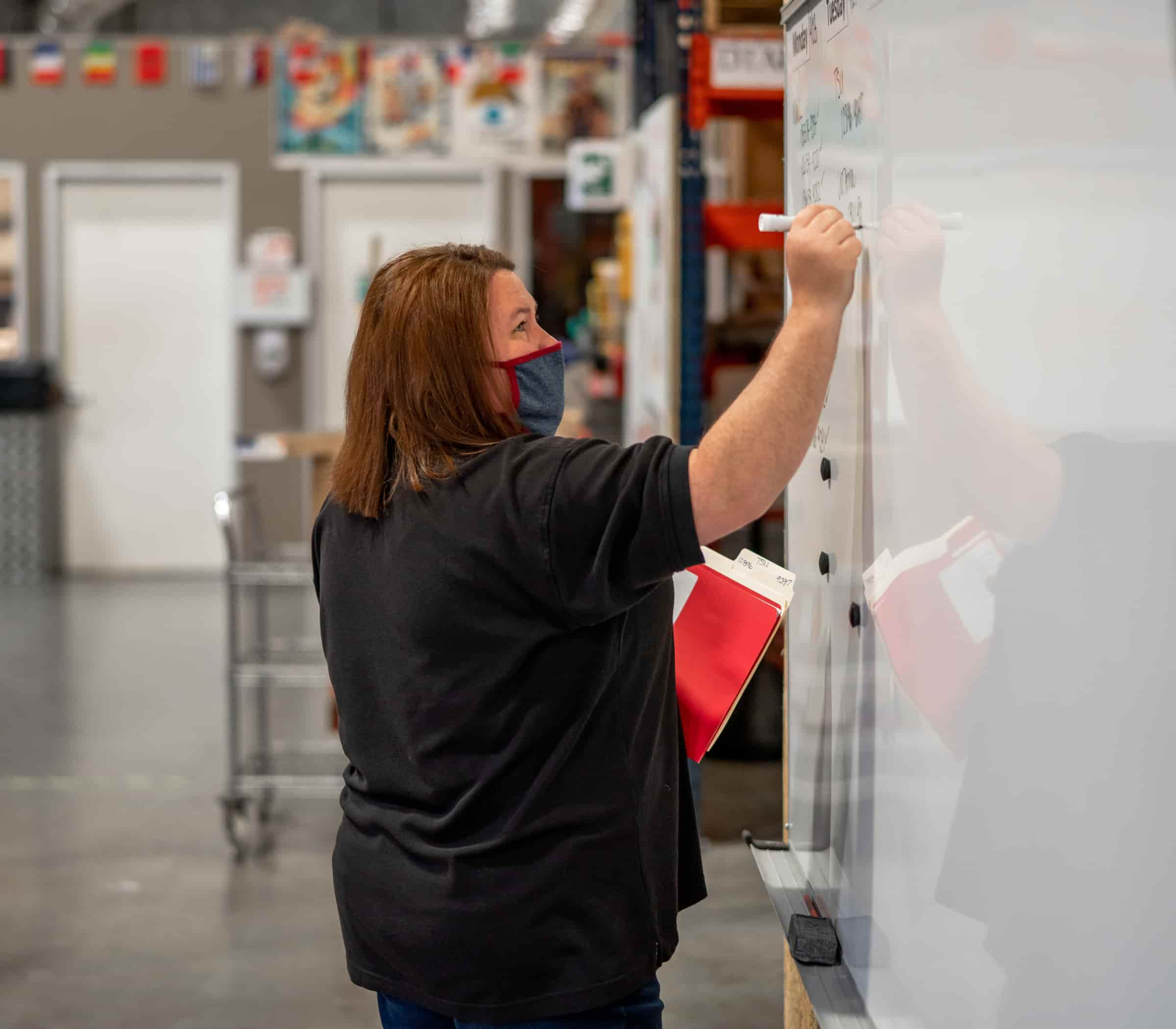 Woman writing on white board in furniture warehouse