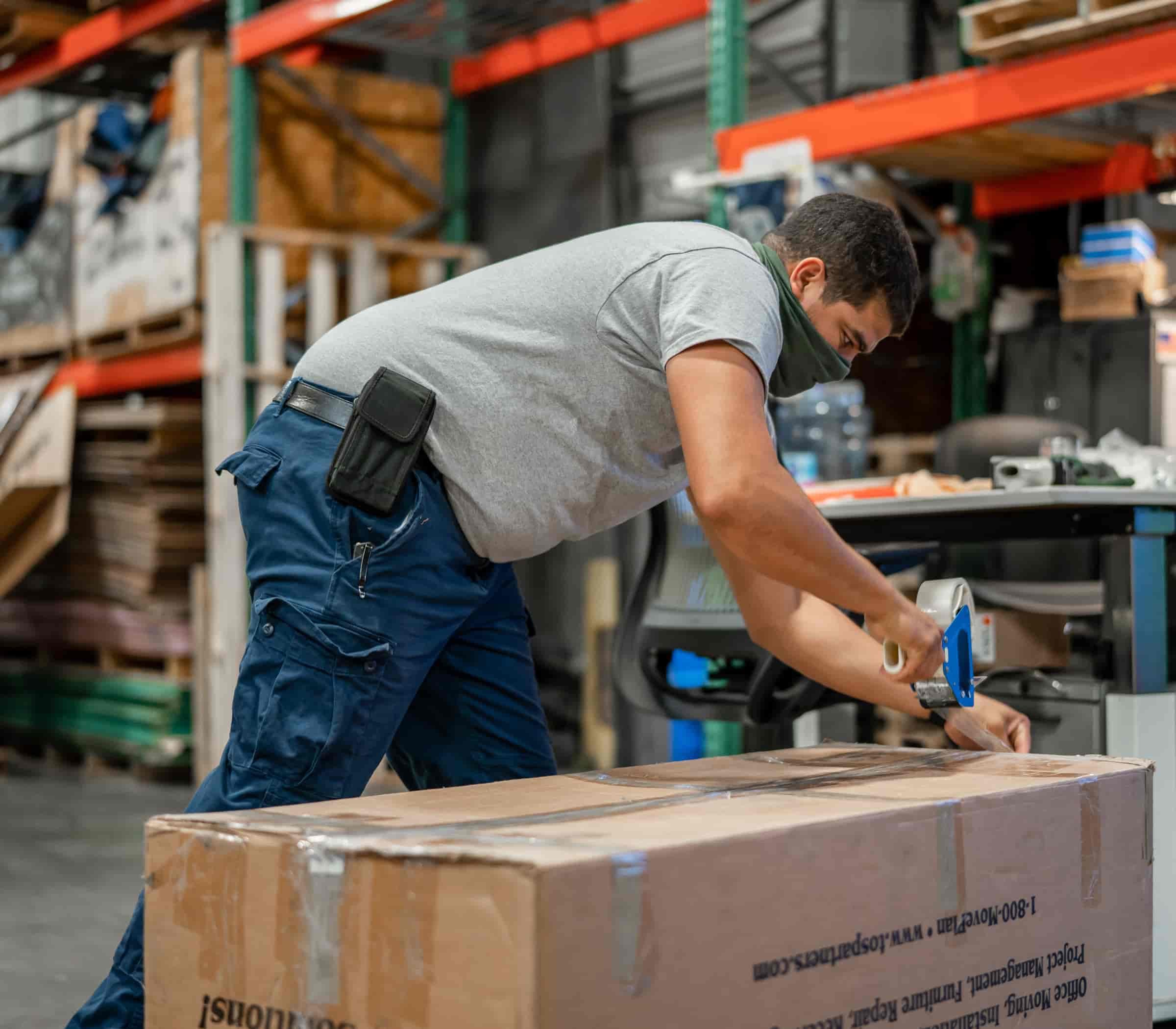 Warehouse worker taping a box