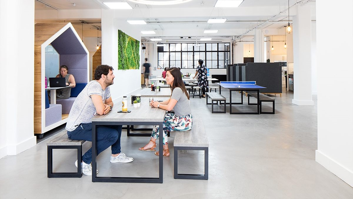 people eating and working in open office space with benches and tables