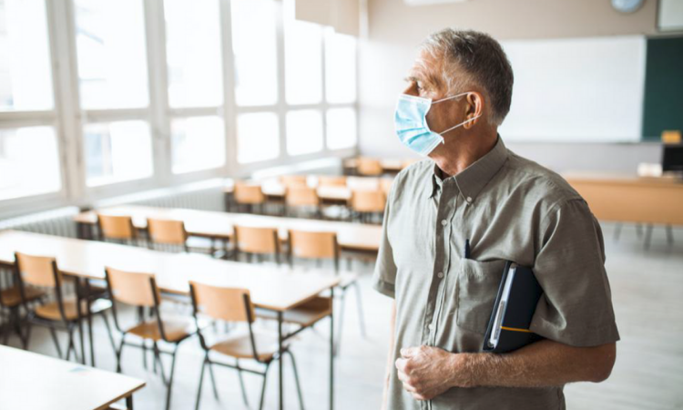 man wearing a facemask in a classroom