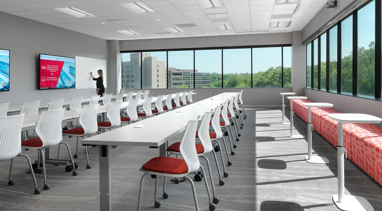 White-painted room with mounted display monitors, bench-style desks, chairs, C-tables and bench seating