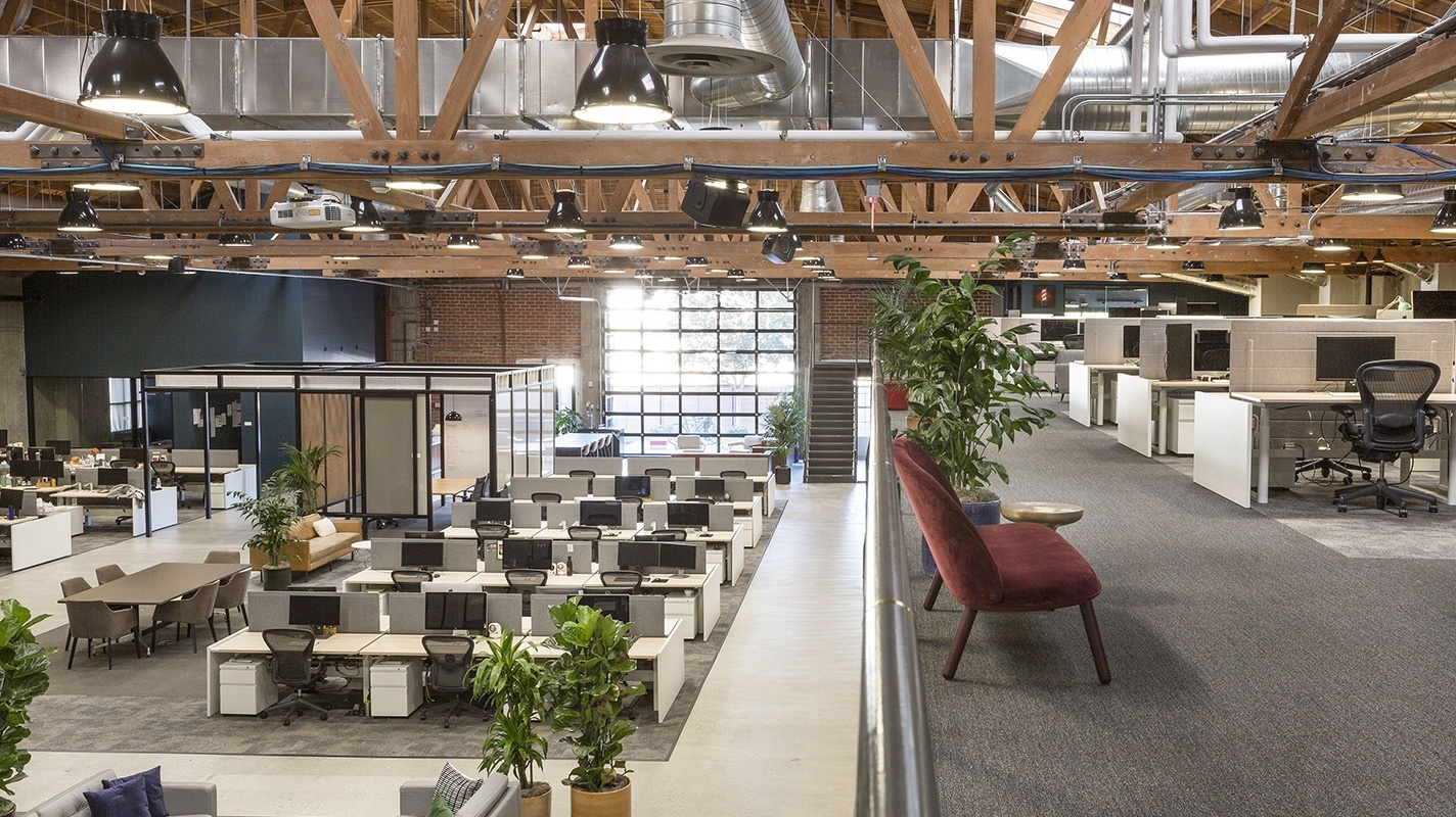 Open space ground floor workstations, glass-walled conference room, lounge seating under an exposed ceiling