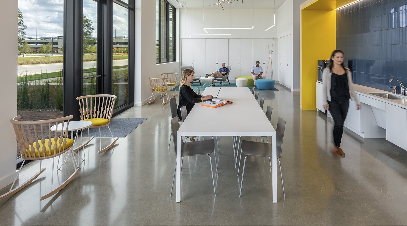 Spacious breakroom with kitchennete, long talbe, rocking chairs, poufs and lounge seating by glass windows
