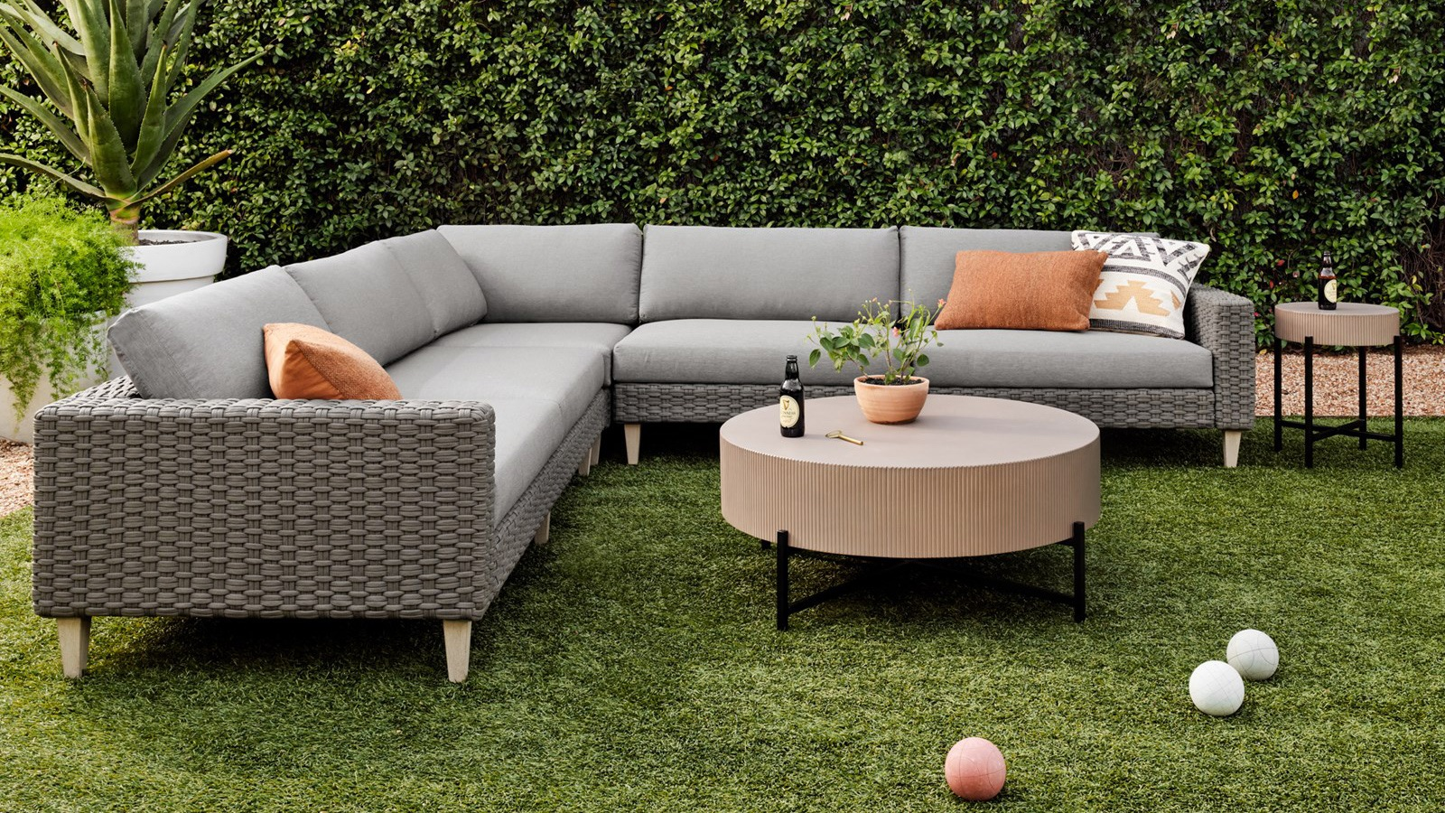 Outdoor space with planter, sectional couch, coffee and side table by a manicured hedges